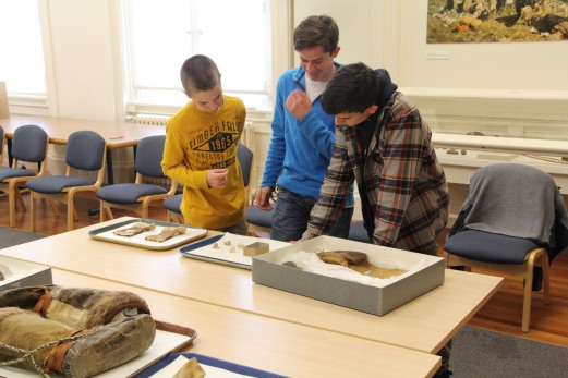 Students looking at bone labrets which would have been worn by men on either side of their mouth