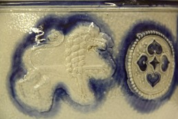 photo showing sprigged on detail of lion and rosette, Westerwald chamber pot