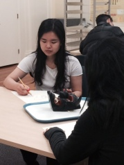 Students looking at black horned mask