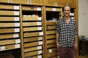 Zac Singer in front of the Peabody storage cabinets that house the Bull Brook collection