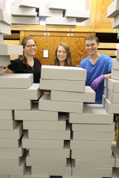 Curator of Collections Marla Taylor and work duty students stand behind the empty boxes
