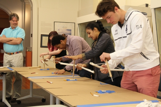 Image of students in Human Origins make bone flutes with bow drills while their instructor Jerry Hagler looks on.