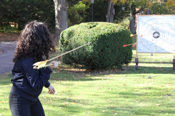 Student in Human Origins course throws a spear using an atlatl or spear thrower. The target in the distance has already been hit with other darts.