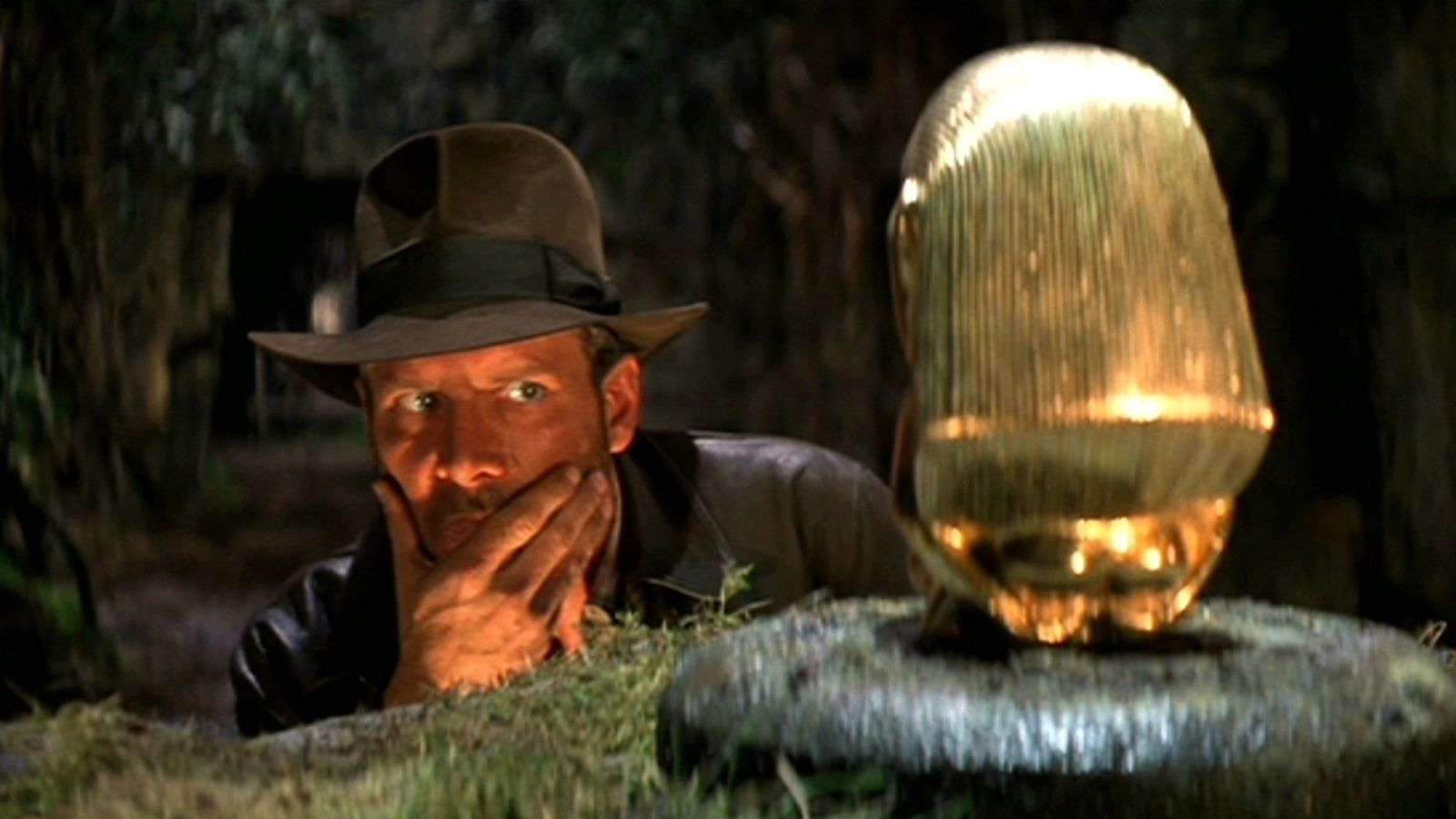 Indiana Jones looks at golden idol.