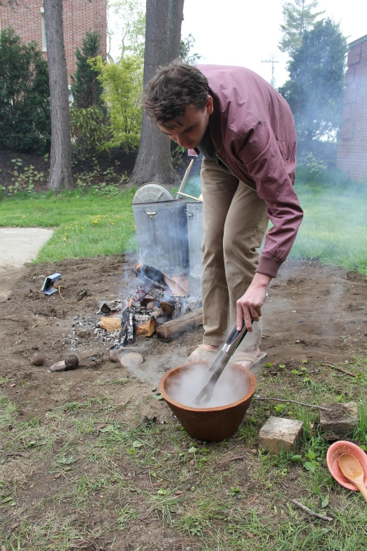 Image of Phillips Academy senior cooking with fired-clay objects.