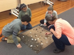 Students looking at a mock excvation unit that has evidence of pottery making