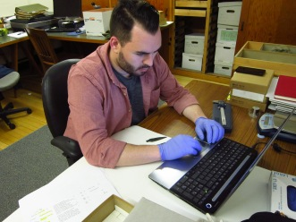 Researcher John Andrew Campbell recording details about objects in the Peabody collection