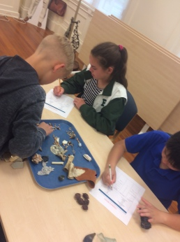 """Students working in the """"lab"""" to identify artifacts found from the mock Katherine Nanny Naylor site"""