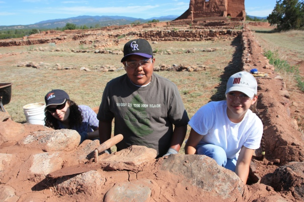 Image of students from Phillips Academy and the Pueblo of Jemez on the Pecos Pathways trip help restore the Spanish church ruins at Pecos National Historical Park.