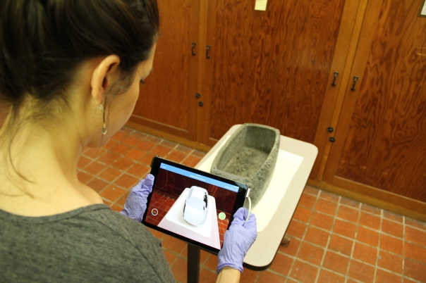 Dr. Kelvin using the 3D scanner to document a bowl
