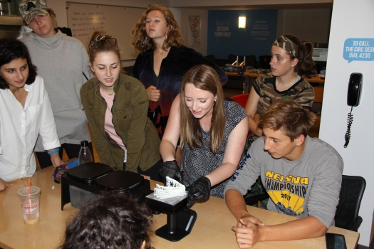 Image of students and Makerspace guru Claudia Wessner with 3D print of Homo naledi hand.