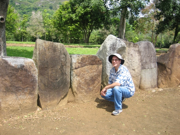 Image of Ryan Wheeler at the Caguana Ceremonial Ball Courts Site in barrio Caguana, Utuado, Puerto Rico, 2006. The reconstructed ball court is lined with engraved stone slabs.