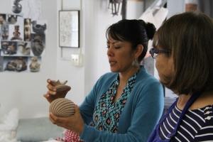 Image of Mia Toya with pottery vessel, Maxine Toya looks on.