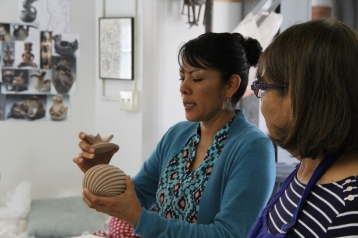 Image of Mia Toya with pottery vessel, Maxine Toya looks on.