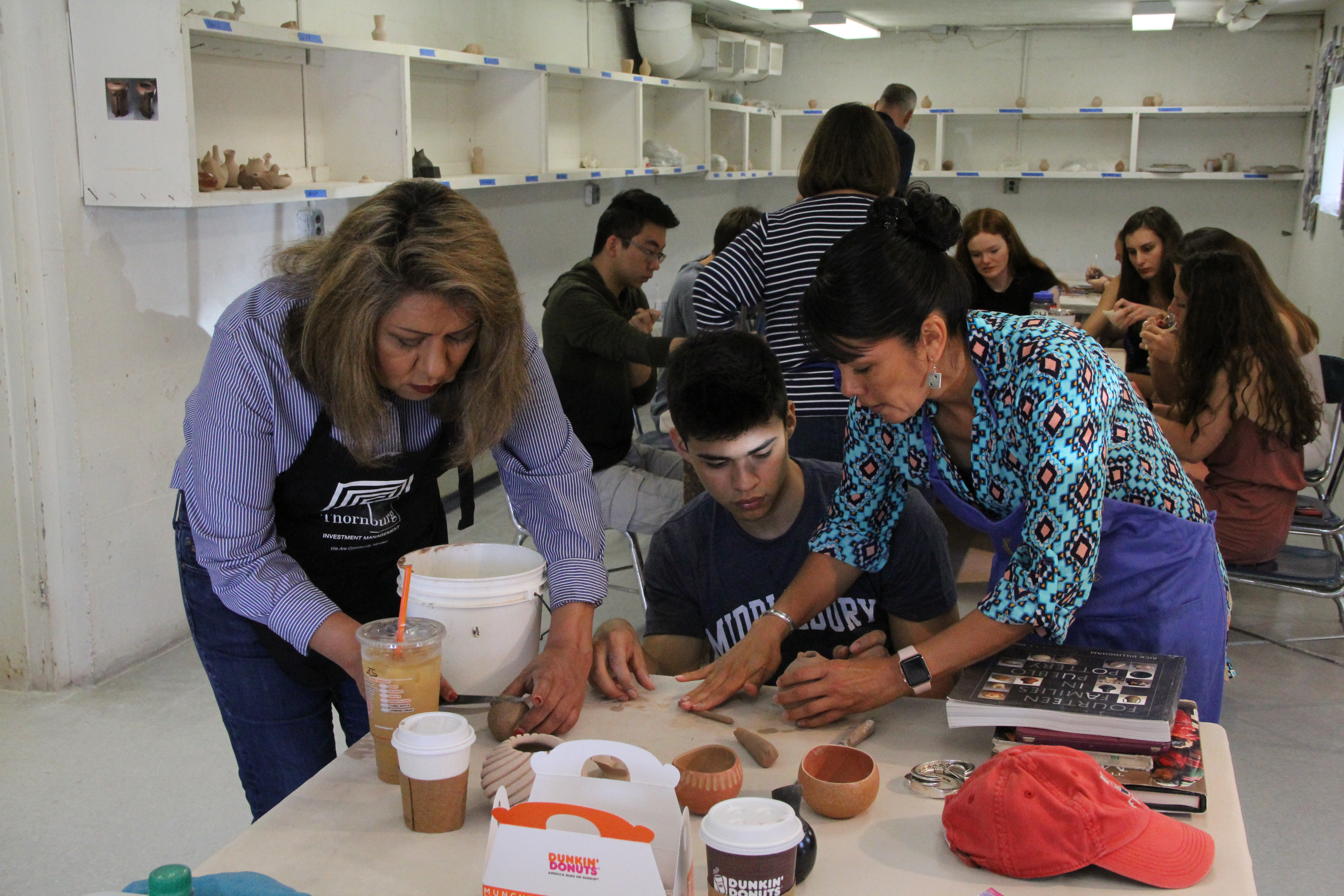 Image of Pueblo potters Dominique and Mia Toya working with a high school student.