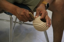 Image of Ward helping to sand the spiral ribs on a butterfly swirl bowl.