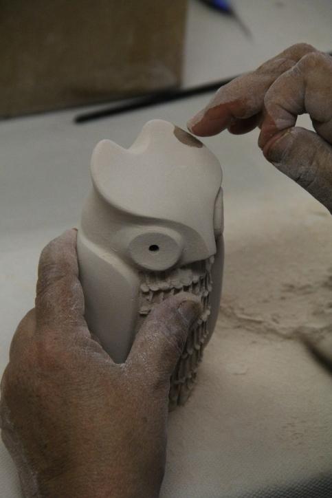 Image of Maxine Toya working on owl figurine.