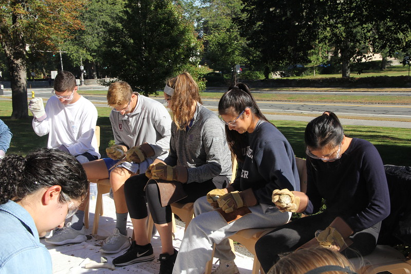Image of students flint knapping or making stone tools.