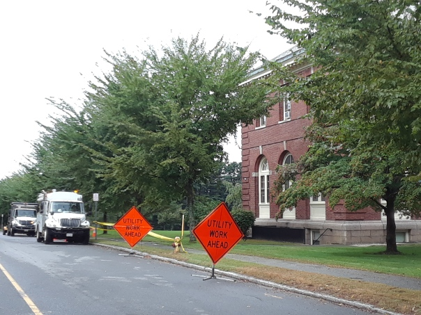 Image of utility signs and trucks next to building.
