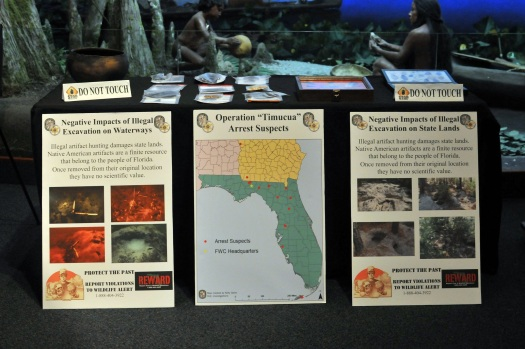 Image of posters about site looting, Operation Timucua press conference.