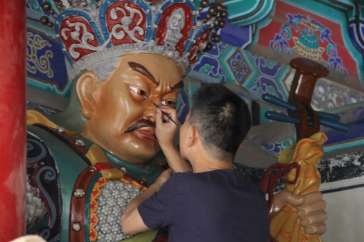 Image of an artist restoring the giant statute of a Buddhist immortal at the Shaolin Monastery.