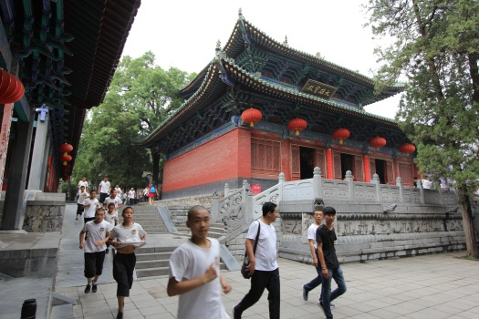 Image of Gong Fu students running past the Shaolin Temple buidlings.