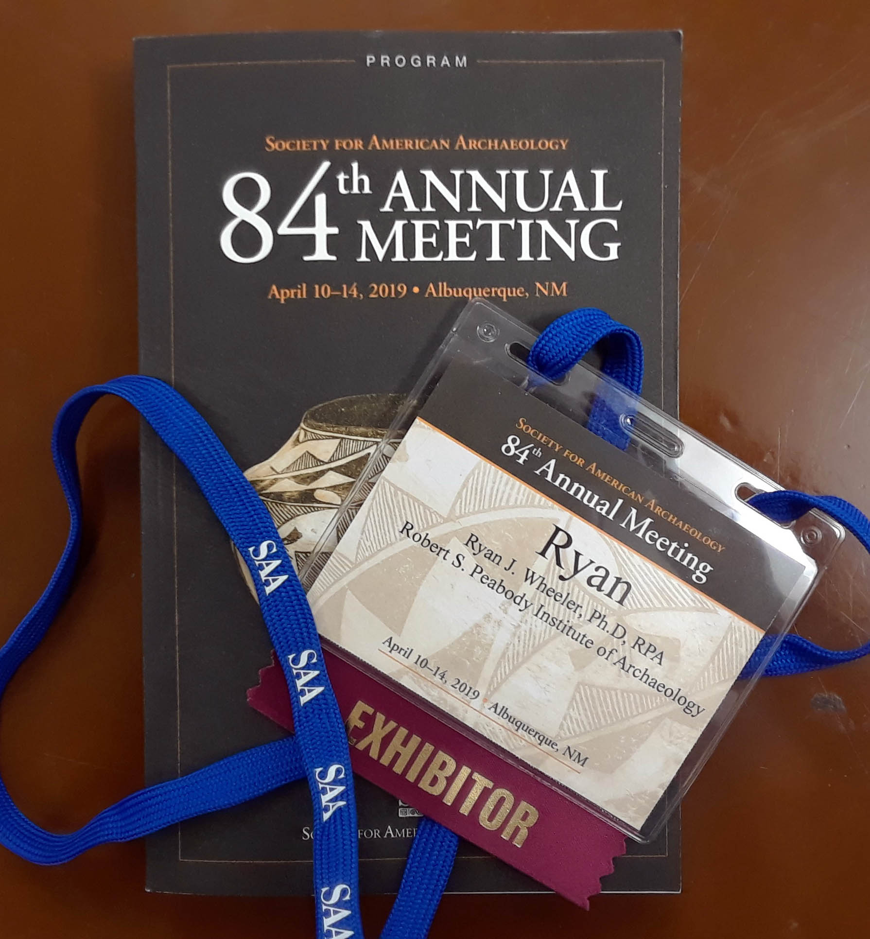 Image of name tag and program book from SAA conference.