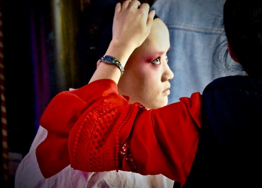 Image of a performer having makeup applied.