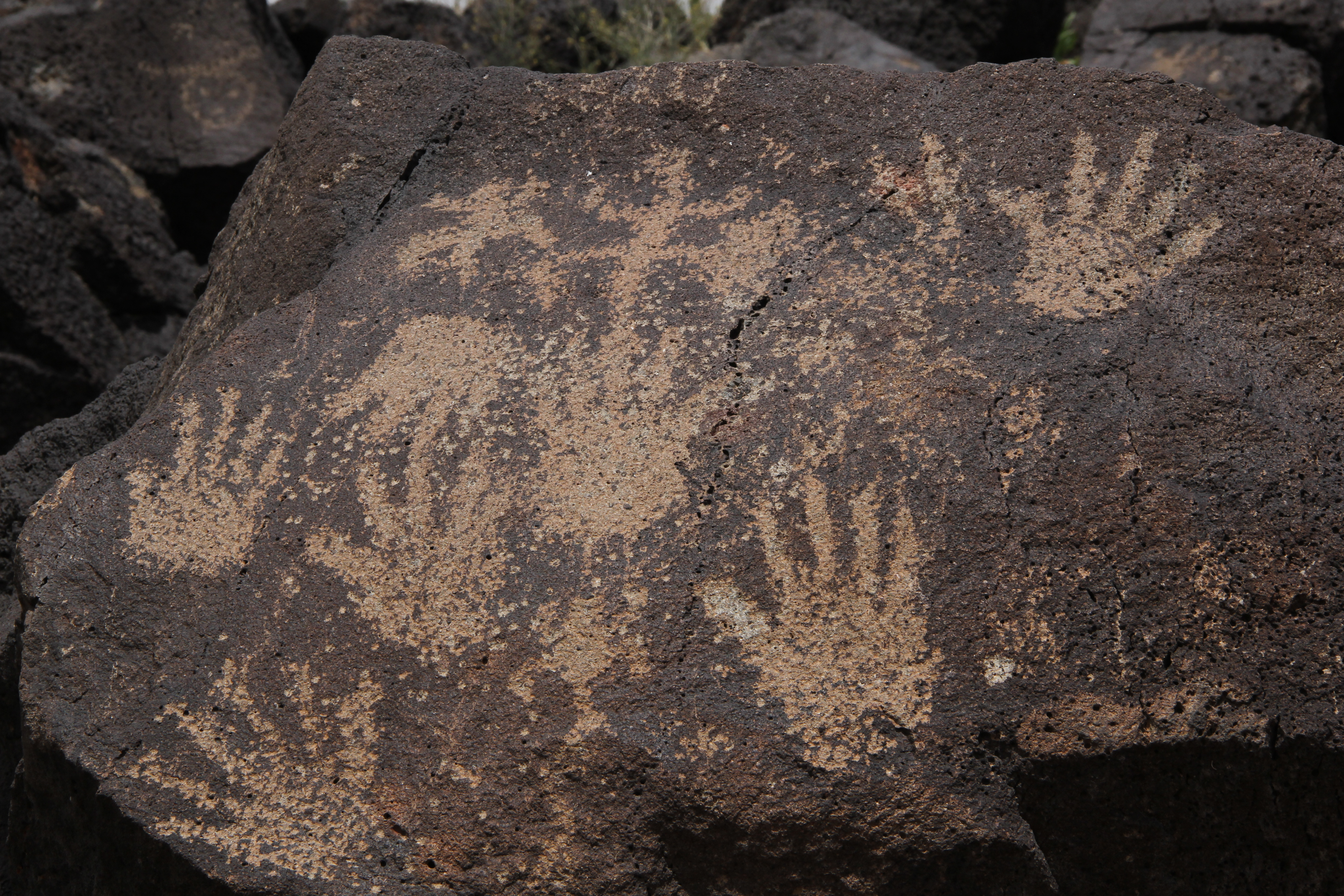 Image of human hand petroglyphs carved on dark volcanic rock at Petroglyph National Monument, New Mexico.