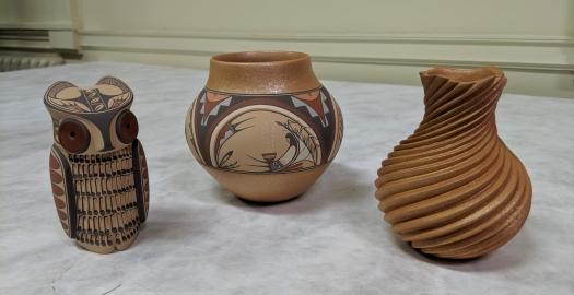 Three pottery figures and vessels, including painted owl figurine, the collaborative piece by Dominique and Maxine, and a swirl pot by Dominique.
