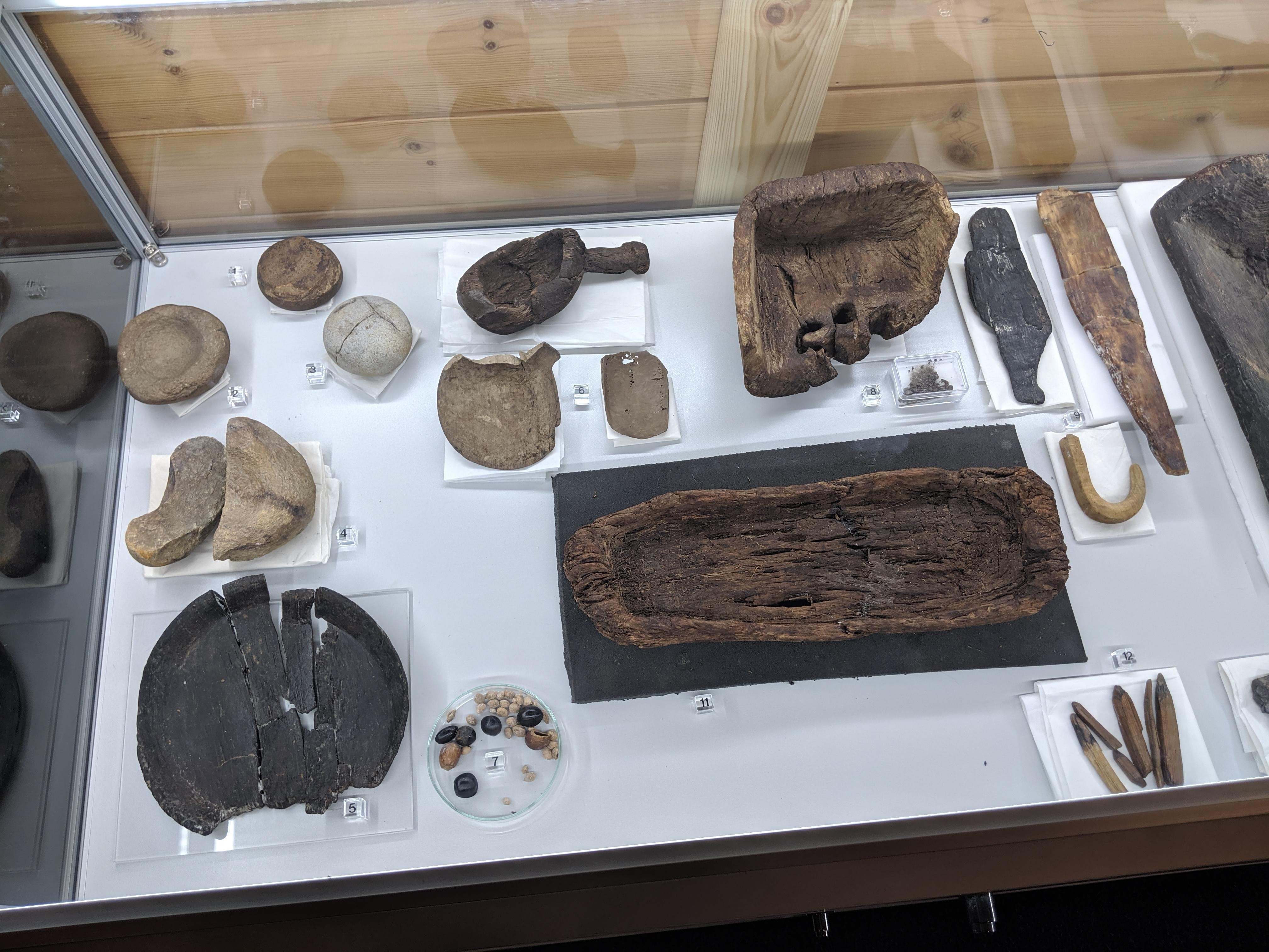 Image of artifacts, including carved wooded ladles, bowls, and other shapes.