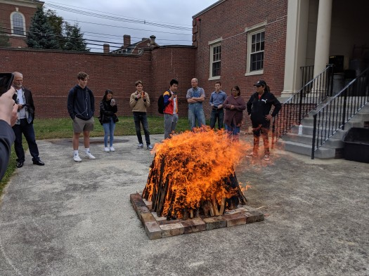 Image of very hot orange fire burning with Native American artists and Phillips Academy students looking on in the background.