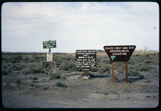 Image of brown road signs and Bureau of Land Management sign pointing the way to the Calico Hill Early Man Site. The background is the Mojave Desert of California, with low hills in the distance and dirt and desert plants in the foreground.