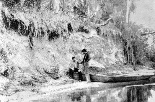 Antique photo of men and small boat along high river bank shell mound site.