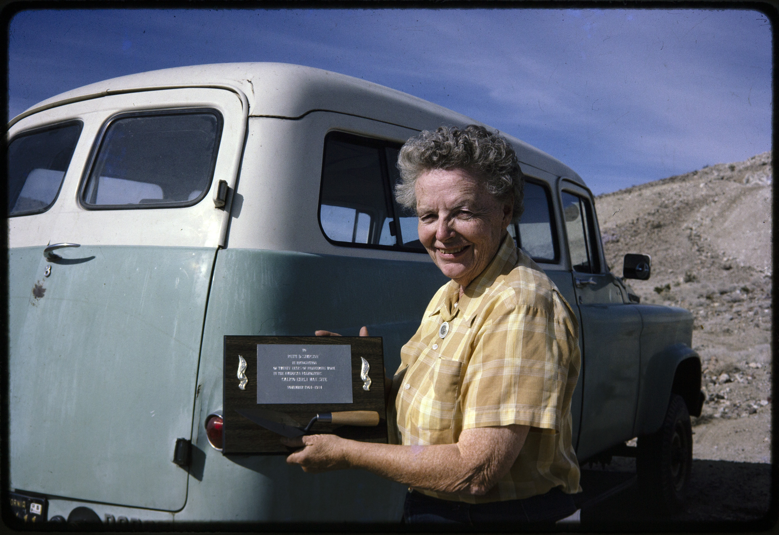 Image of archaeologist Ruth Simpson, an older woman with short gray hair, a yellow plaid shirt, holding a plaque. In the background is an old field vehicle from the 1950s or 1960s.