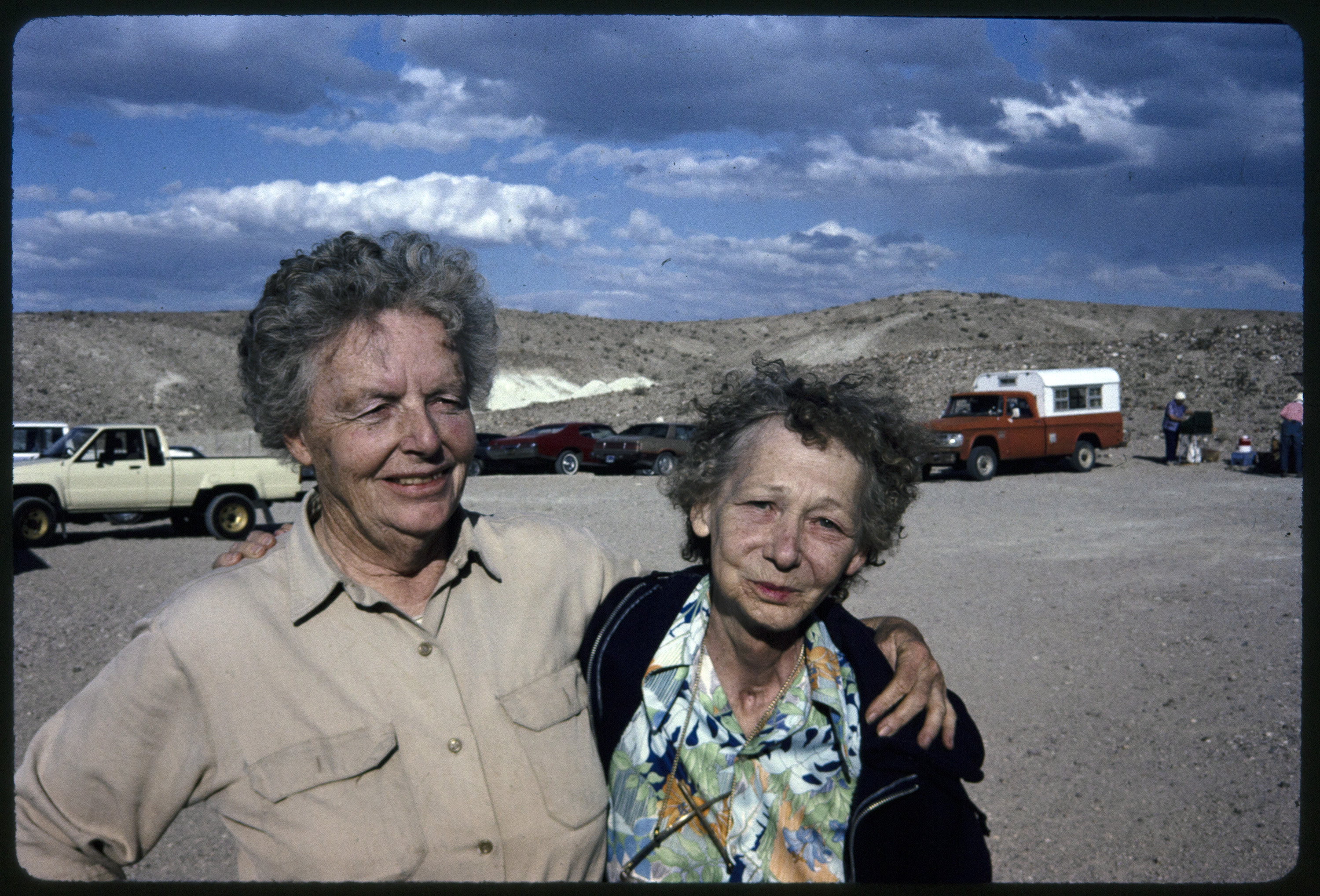 Archaeologist Ruth Simpson, an older woman with short gray hair wearing a khaki field shirt, poses with a friend--an older, unidentified woman with gray curly hair, wearing a floral shirt and blue jacket. Vehicles are parked in the background, and low desert hills of the Mojave are further back with a dark blue sky.