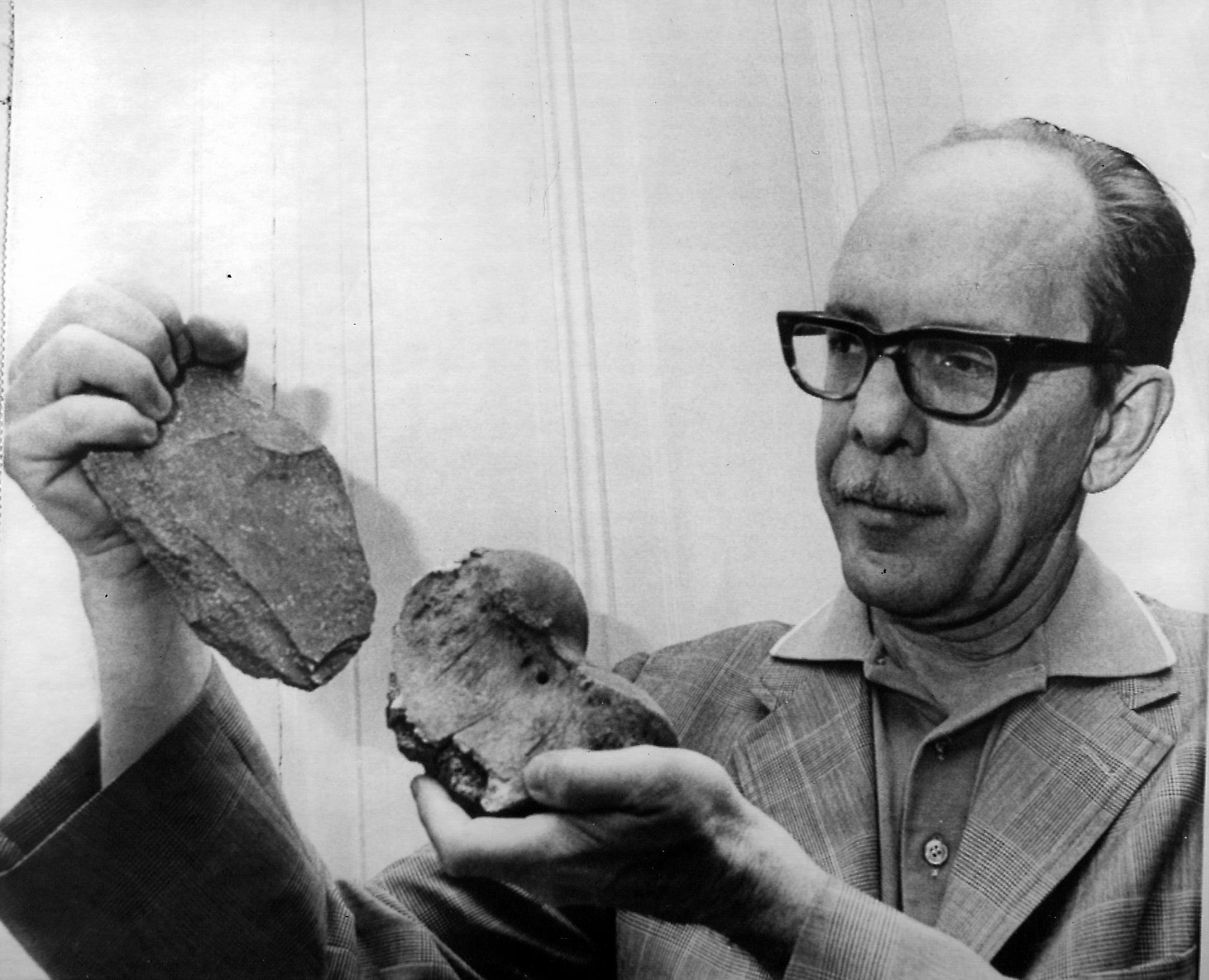 Image of Scotty MacNeish, wearing heavy black framed glasses and a tweed blazer holding a large, crude stone chopper tool and the end of a large sloth leg bone.