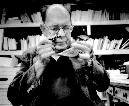 Image of Scotty MacNeish, an older, balding man with wire frame glasses using a jeweler's loupe to examine a point stone tool from Pendejo Cave, New Mexico. Bookshelves are in the background, slightly out of focus.