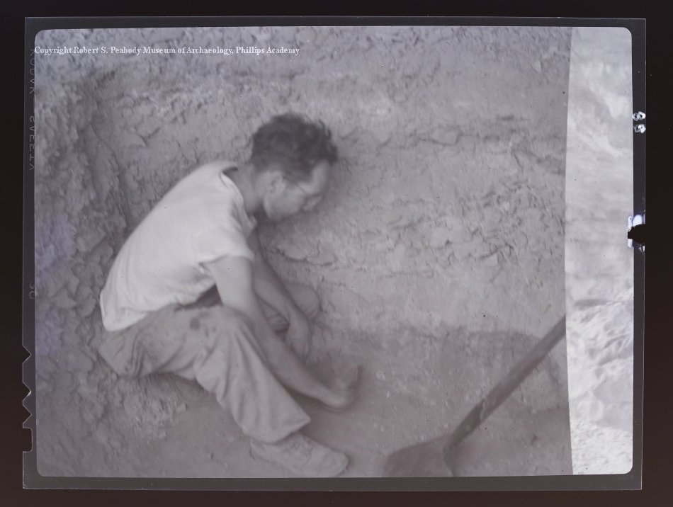 A man in a white t-shirt and khaki pants sits in an excavation pit and removes samples.