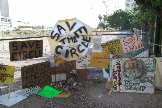 Image of protest signs left in front of a chain link fence.