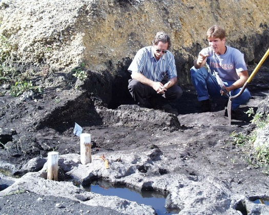 Two male archaeologists crouch down and examine water-filled basins carved in limestone bedrock. Dirt piles are behind them.