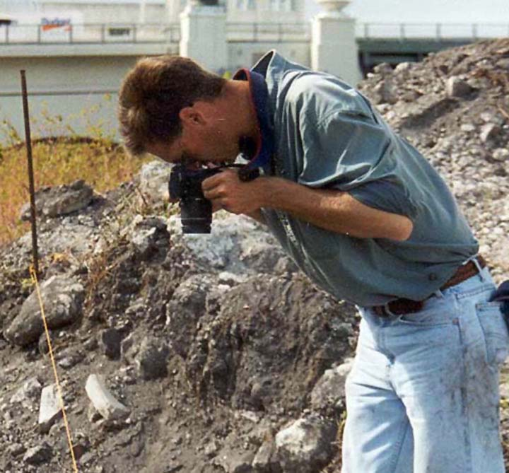 Image of the author shooting pictures at the site. He is wearing dirty blue jeans and a green work shirt. He has closely cropped hair. The Brickell Bridge is in the background and piles of rock and rubble are present.