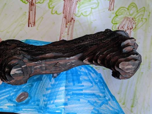 Image of the cardboard Megalonyx femur on a blue and green painted background.
