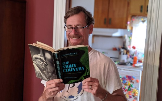 Ryan Wheeler reading his copy of Loren Eiseley's The Night Country.