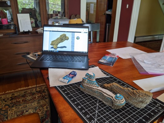 Image of stacked cardboard pieces on a cutting mat with a computer in the background showing a virtual assembly of the model.