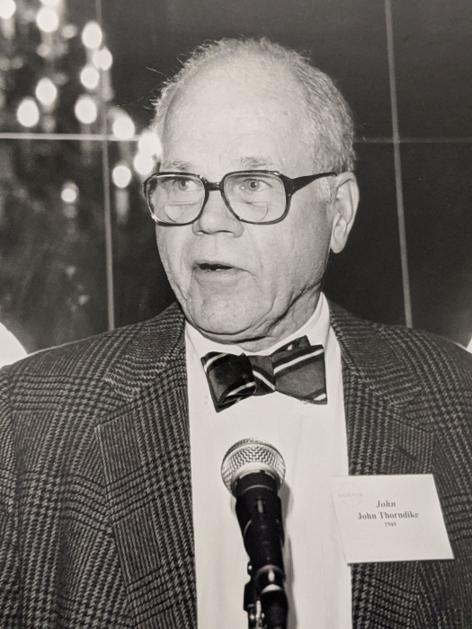Image of John Thorndike, an older man with black rim glasses, a striped bow tie, and tweed jacket standing in front of a microphone at a museum event.
