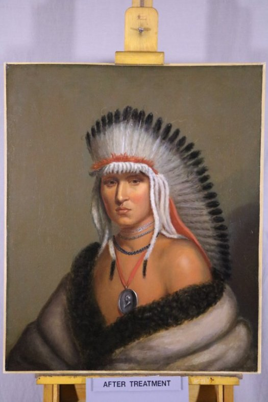 Image of cleaned oil painting showing Native American man with eagle feather headdress, silver peace medal necklace, and fur robes.