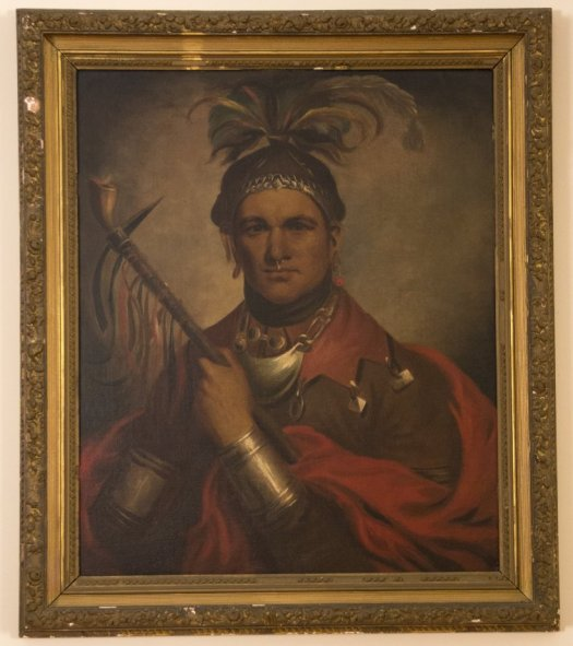 Image shows an oil painting of a Native American man with feather headdress and spontoon pipe, metal gorget at the neck and metal gauntlets.