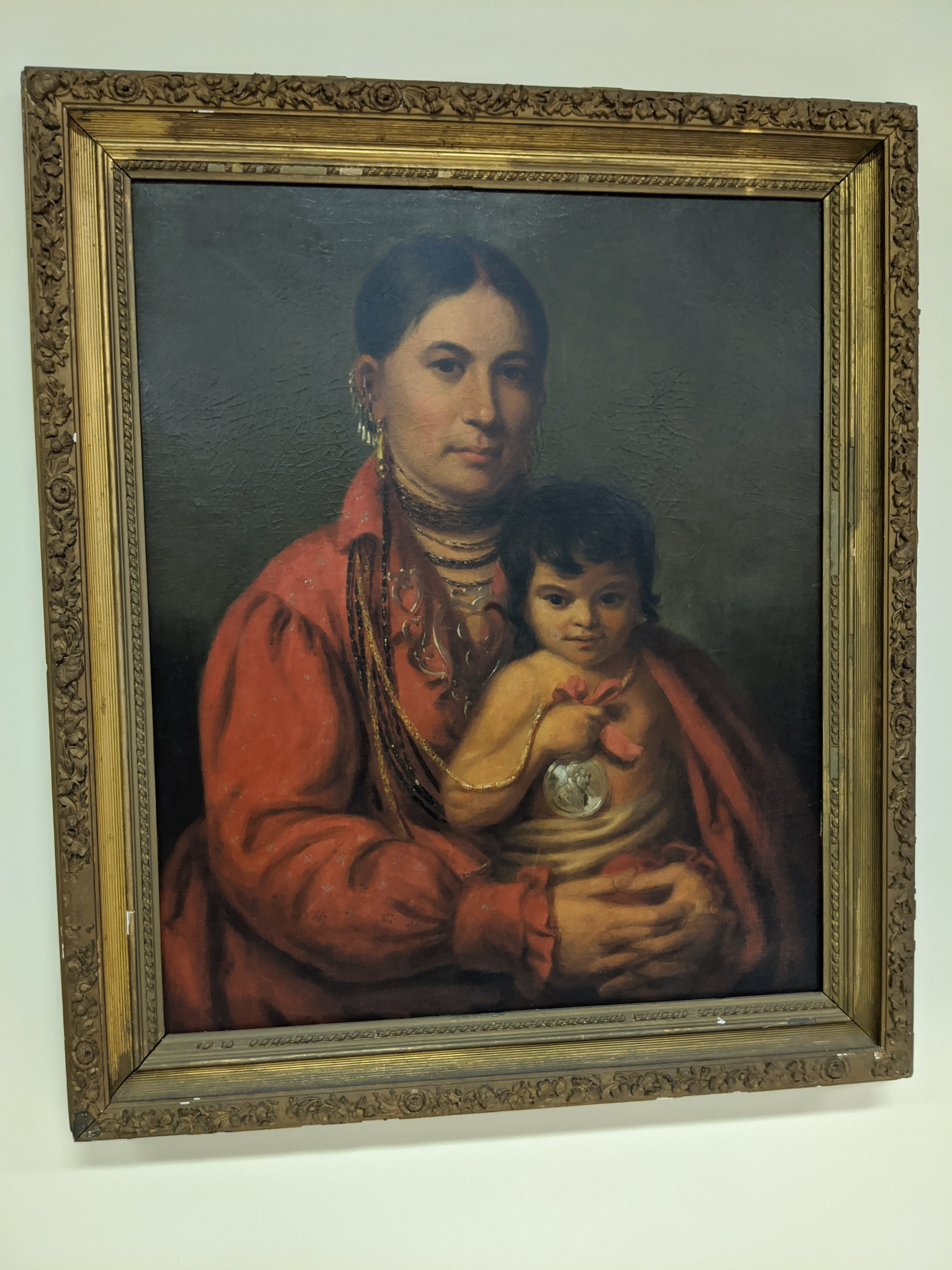 Image shows an oil painting in an elaborate gold gilt frame that depicts an attractive Native American woman holding her baby. She wears a red blouse which covers the baby's shoulders. A silver Indian Peace Medal around her neck is held by the baby.