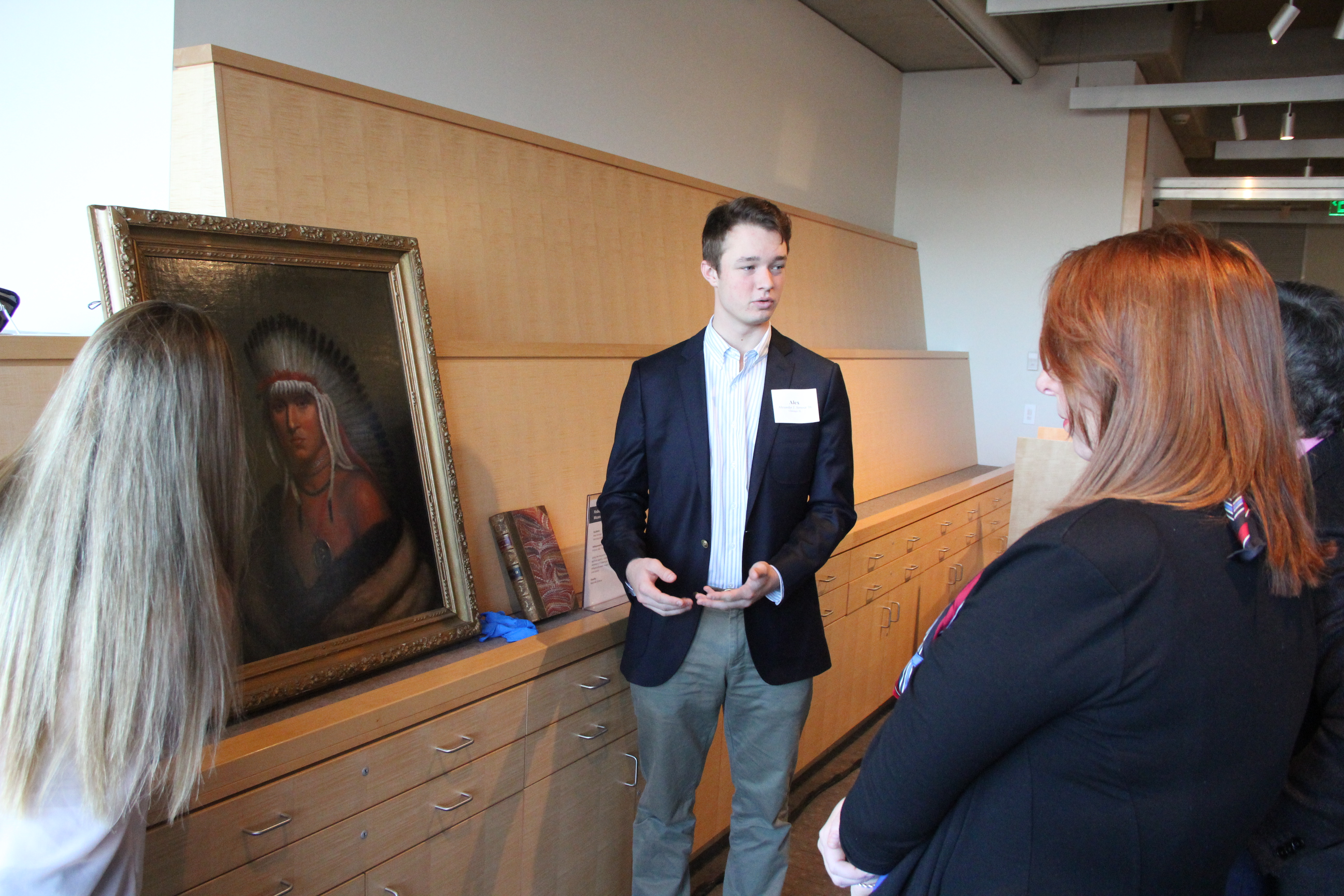 Image shows two students standing on either side of an oil painting of a Native American and explaining their work to onlookers.